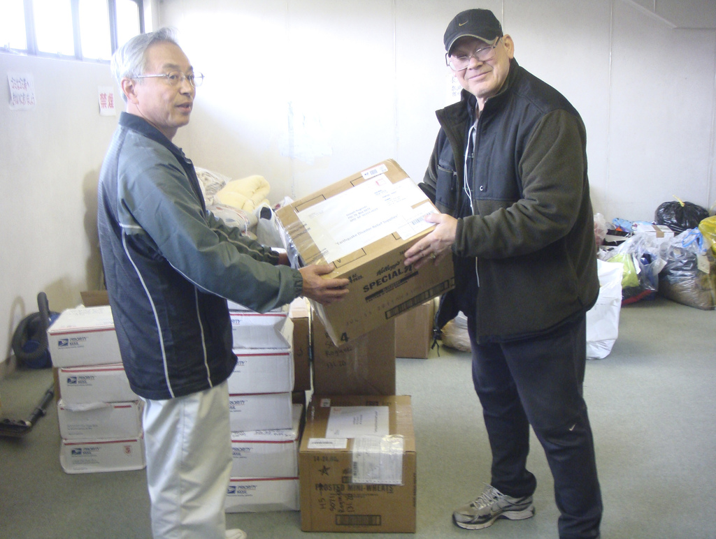 In this photo provided by Joseph Roginski, taken May 13, 2011, Joseph Roginski, right, holds a package in a storeroom of the Misawa Cit...