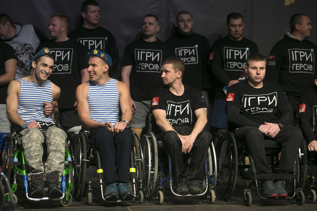 In this photo taken Saturday Dec. 24, 2016, in Kiev, Ukraine, unidentified participants pictured first and second left, wearing paratro...