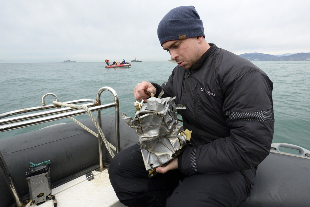 A Russian Emergency Ministry diver inspects a fragment of a plane in the Black Sea, outside Sochi, Russia, Tuesday, Dec. 27, 2016. Inve...