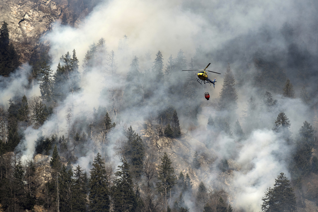 A fire fighting helicopter discharges water over the forest fires near Mesocco in Southern Switzerland, Wednesday, Dec.  28, 2016. (Gab...