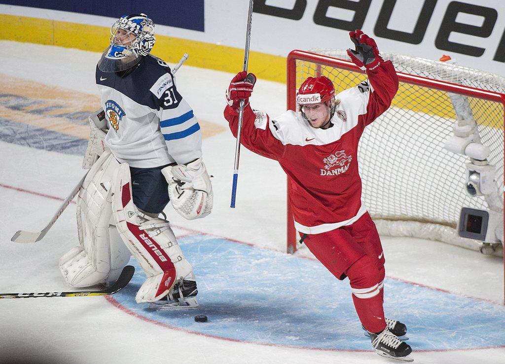 Denmark's Frederik Hoeg (22) celebrates a goal by teammate David Madsen (not shown) against Finland goaltender Veini Vehvilainnen durin...