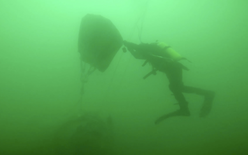 In this image made from video and provided by the Russian Emergency Ministry Press Service, ministry diver lifts a fragment of a plane ...