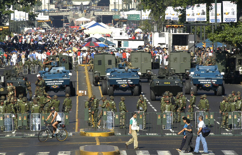 FILE - In this Feb. 14, 2004 file photo, the military creates a perimeter at a government-subsidized food market in Caracas, Venezuela....
