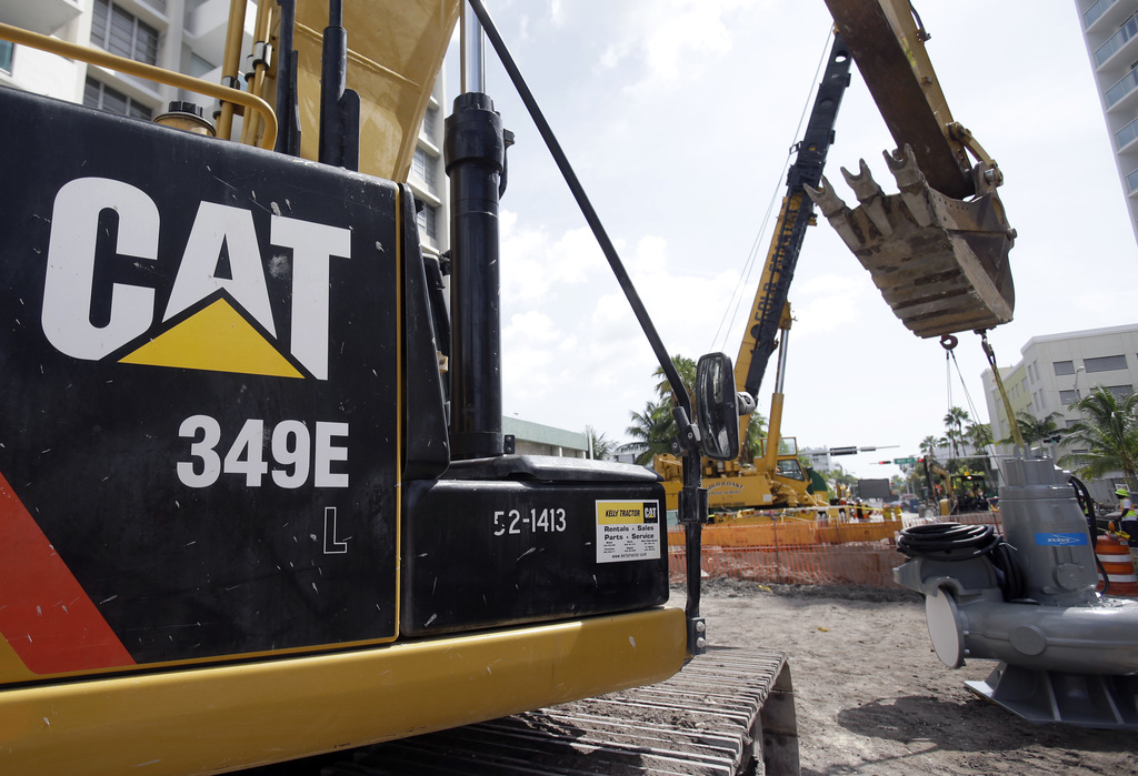 FILE - In this Wednesday, Sept. 17, 2014, file photo, a Caterpillar 349E Hydraulic Excavator operates on a construction site in Miami B...