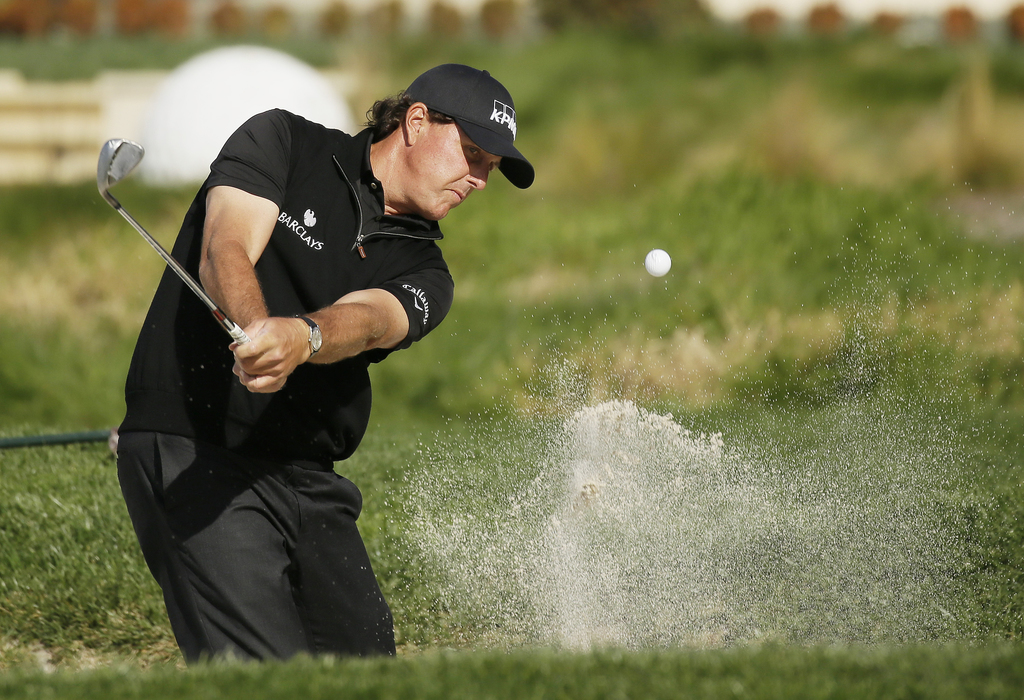 FILE - In a Sunday, Feb. 14, 2016 file photo, Phil Mickelson hits out of a bunker onto the second green of the Pebble Beach Golf Links ...