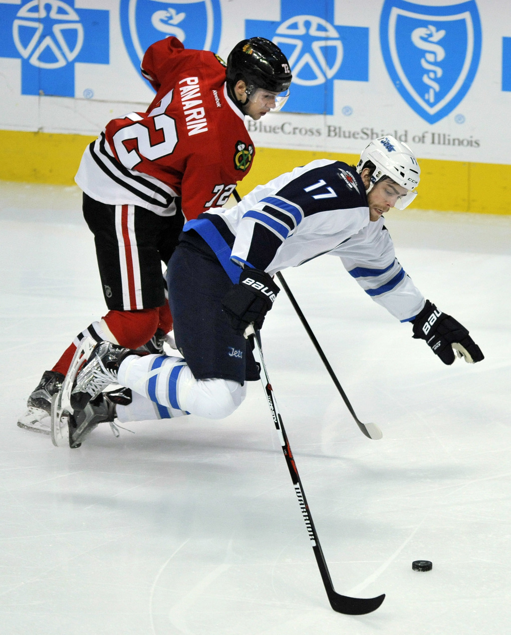 Winnipeg Jets' Adam Lowry (17) battles Chicago Blackhawks' Artemi Panarin (72) of Russia, for a loose puck during the first period of a...