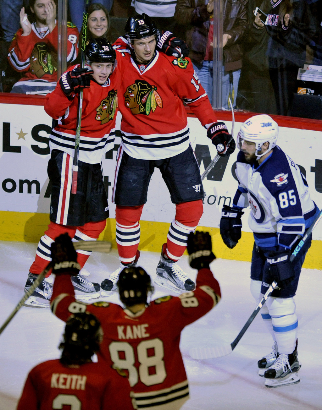 Chicago Blackhawks' Artem Anisimov (15) of Russia, celebrates with teammates Artemi Panarin (72) of Russia, and Patrick Kane (88) after...