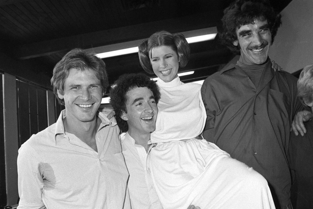 FILE - In this Oct. 5, 1978 photo, from left, actors Harrison Ford, Anthony Daniels, Carrie Fisher and Peter Mayhew take a break from f...