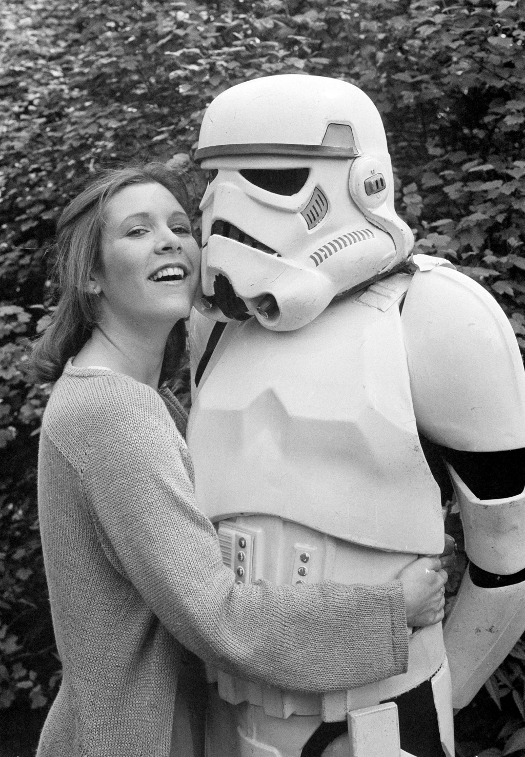 """FILE- In this May 23, 1980, file photo, actress Carrie Fisher hugs a person dressed as a stormtrooper in London while promoting the """"St..."""