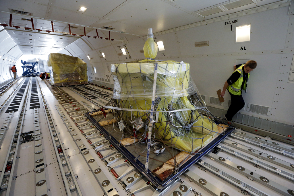 FILE - In this Friday, Oct. 7, 2016, file photo, workers move cargo into position inside a new AirBridgeCargo Boeing 787-8 freighter ai...