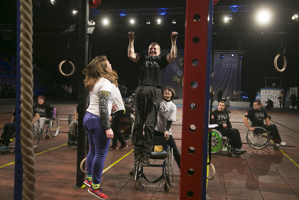 In this photo taken Saturday Dec. 24, 2016, a wheelchair participant performs power exercises as a judge watches, during the Games of H...