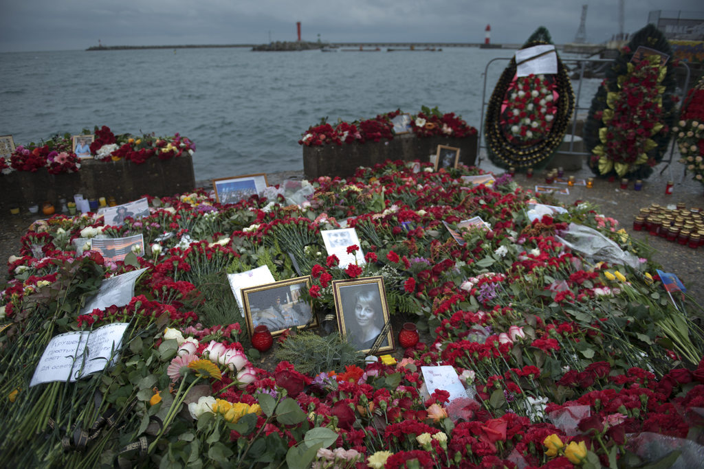 Flowers, candles and portraits are placed at a pier in honour of the victims of the military plane crash, in Sochi, Russia, in Sochi, R...