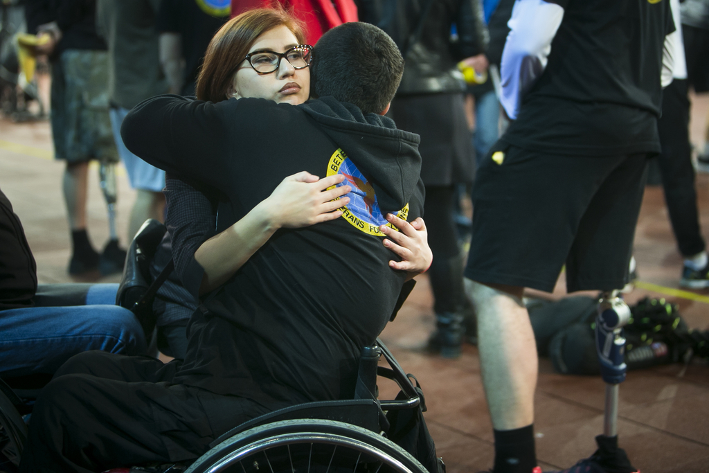 In this photo taken Saturday Dec. 24, 2016, in Kiev, Ukraine, a girl congratulates a wheel-chaired former soldier in a sign of support,...