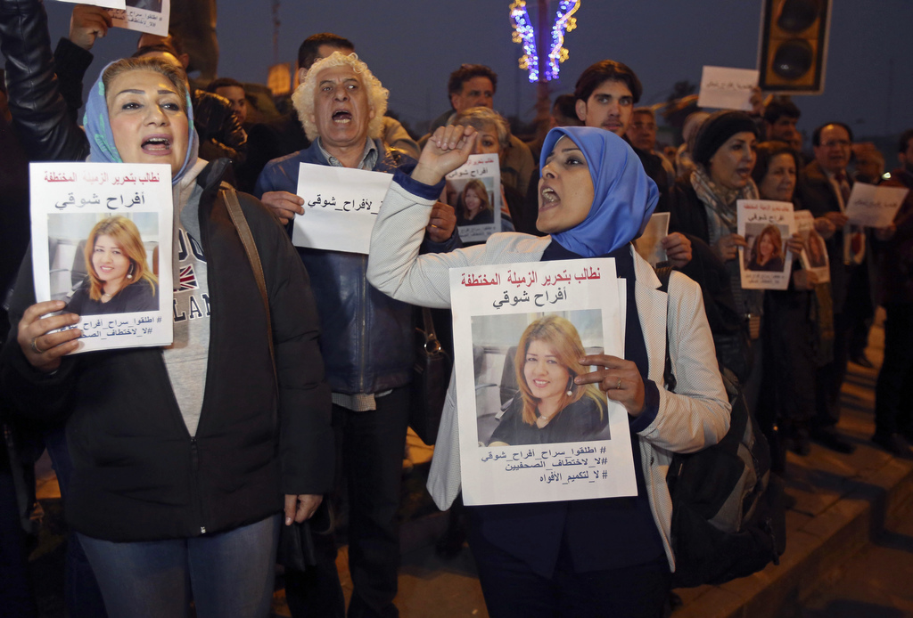 Protesters chant slogans demanding the release of kidnapped journalist Afrah Shawqi al-Qaisi, seen in posters, during a demonstration, ...