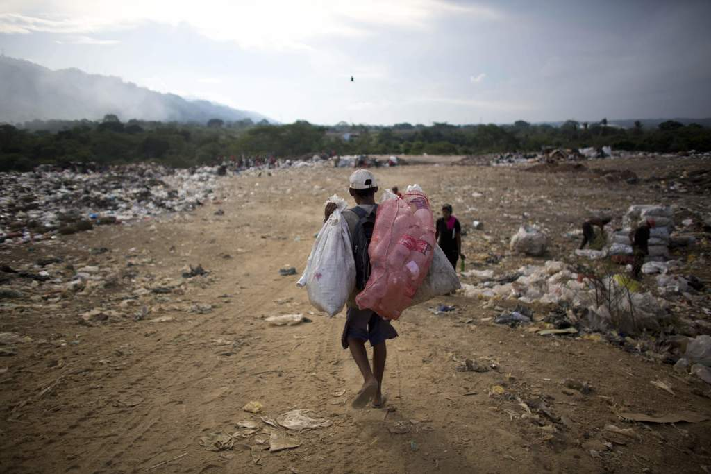 In this Nov. 1, 2016 photo, a man carries bags of recyclable material he collected at the dump in Puerto Cabello, Venezuela, the port c...