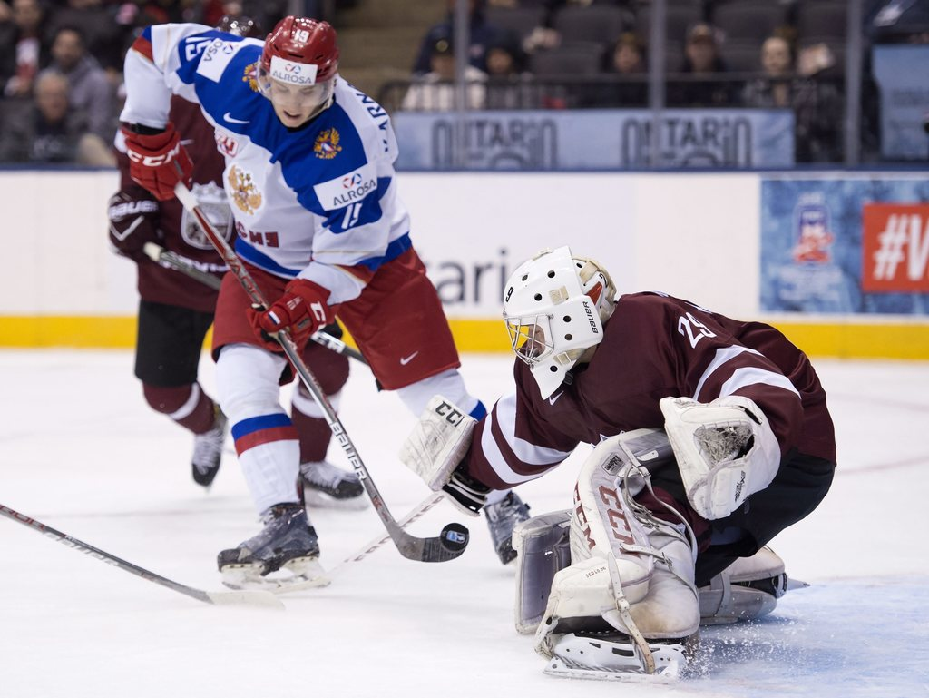 Russia's Pavel Karnaukhov scores on Latvia's goaltender Gustavs Grigals during first period preliminary round World Junior Hockey Champ...