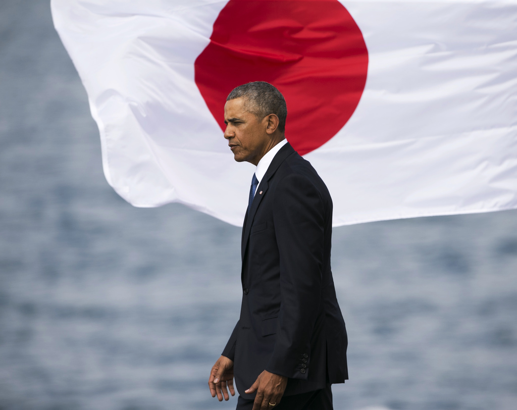 U.S. President Barack Obama walks past a Japanese flag at Joint Base Pearl Harbor-Hickam, Tuesday, Dec. 27, 2016, in Honolulu. Abe and ...