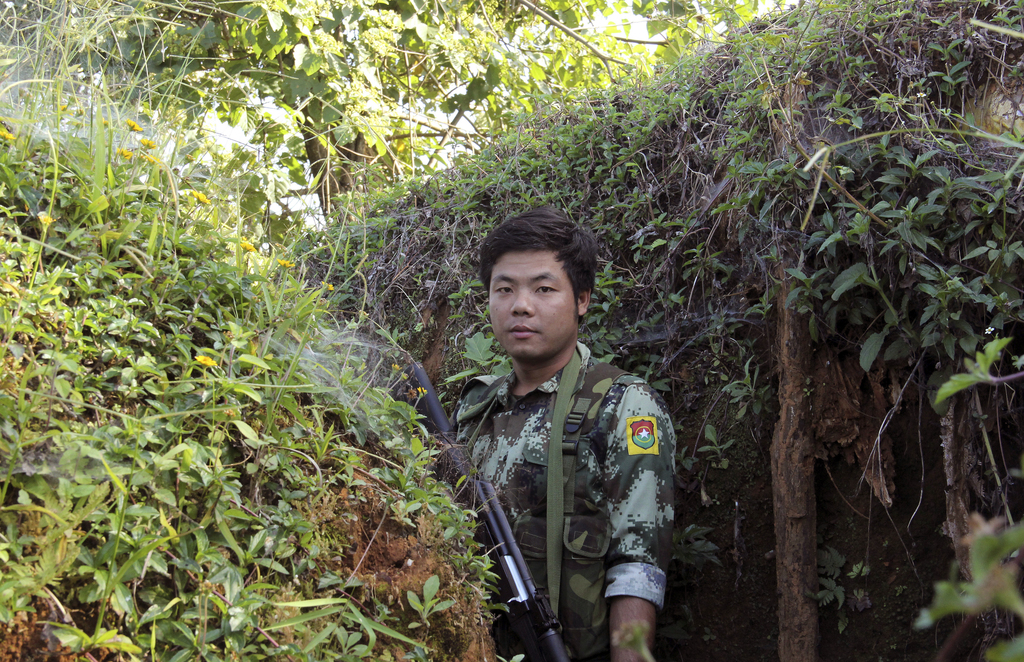 In this Nov. 30, 2016 photo, a Kachin Independence Army (KIA) soldier patrols at the front line through the bunkers of Alen Bum near La...