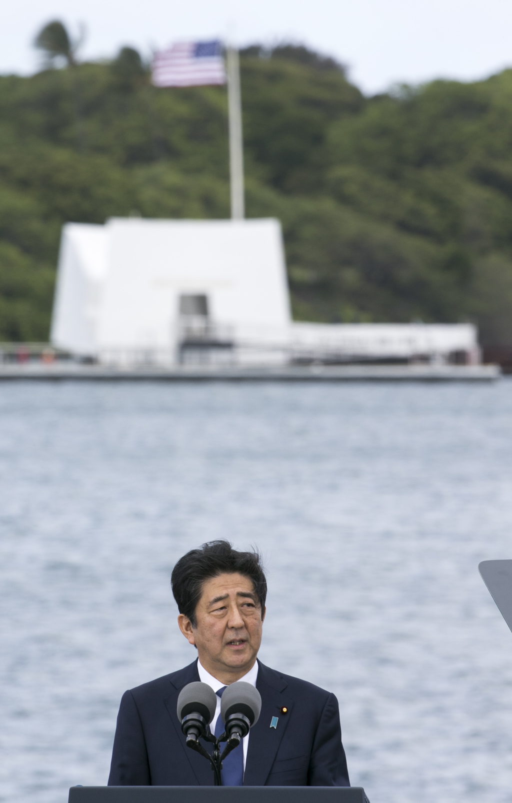 With the USS Arizona Memorial in the background, Japanese Prime Minister Shinzo Abe speaks at Joint Base Pearl Harbor Hickam, Tuesday, ...