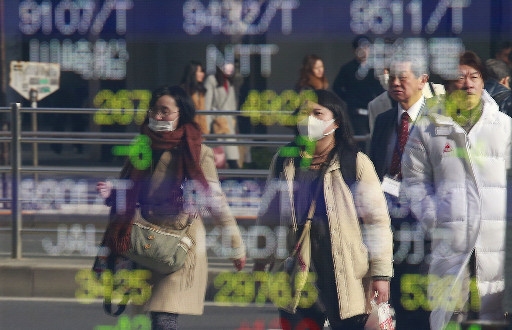 People are reflected on an electronic stock indicator of a securities firm in Tokyo, Thursday, Dec. 29, 2016. Asian shares drooped in t...