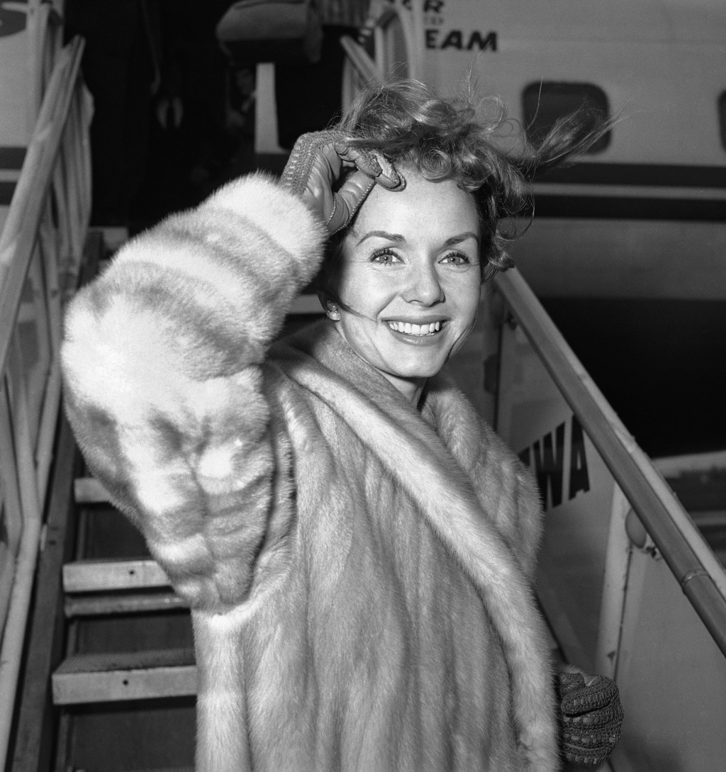 FILE- In this March 6, 1959, file photo actress Debbie Reynolds boards an airliner in New York en route to Spain where she will film a ...
