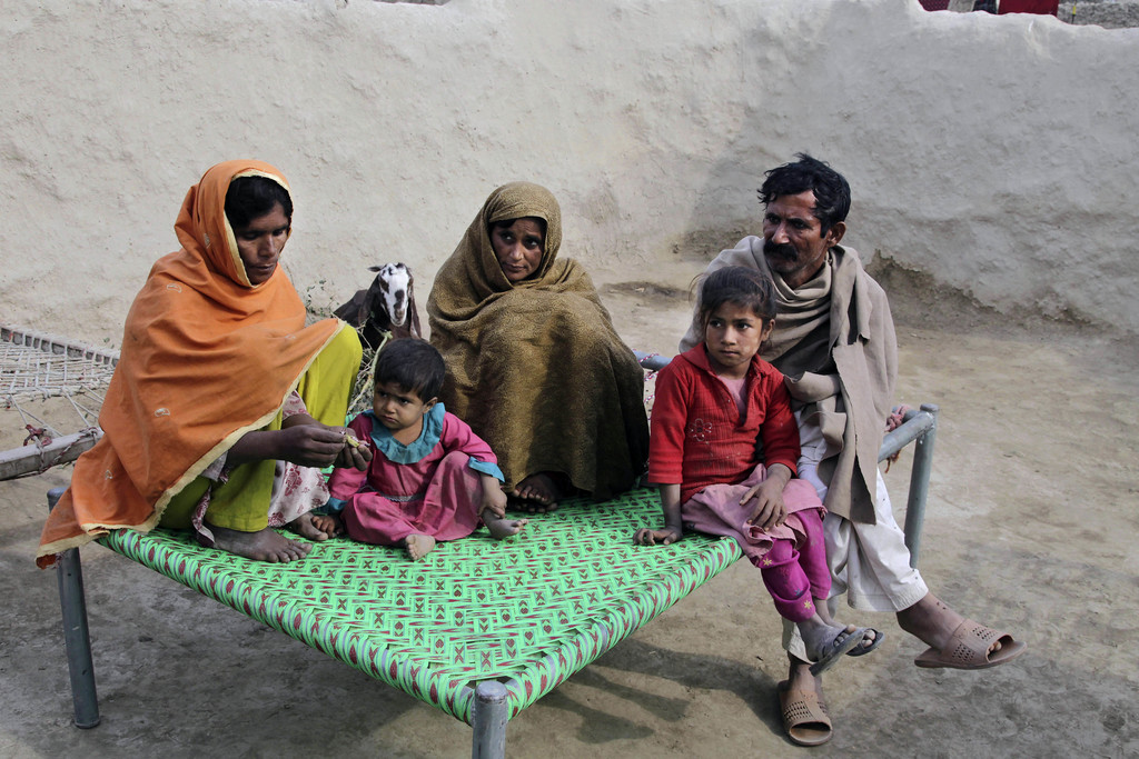 In this Wednesday, Dec. 21, 2016 photo, Wazir Ahmed, right, who married his underage daughter to a 36 year-old man, sits with his wives...