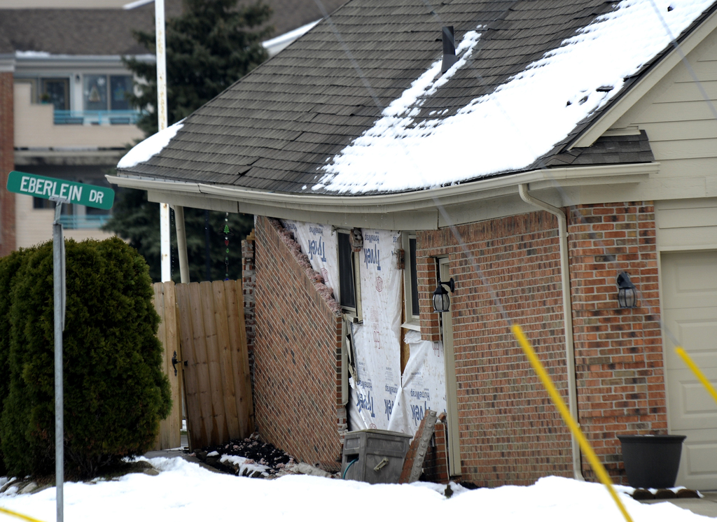 In this Saturday, Dec. 24, 2016 photo, bricks are falling off the exterior wall of a house sitting over a sinkhole, in Fraser, Mich. Th...