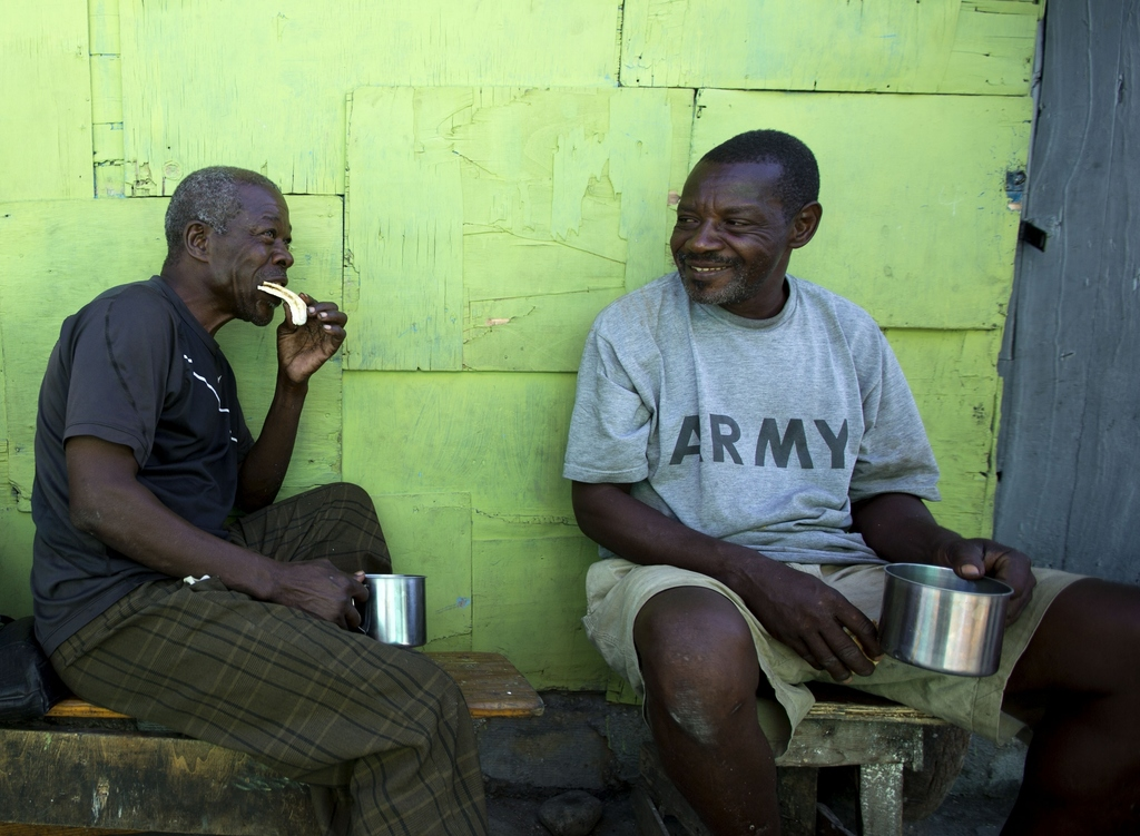 "In this Dec. 25, 2016 photo, ""bayakou"", or human waste cleaner, Auguste Augustin, left, visits with a friend in Port-au-Prince's La Sal..."