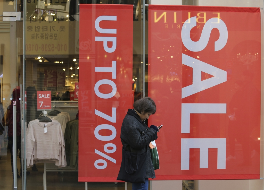 In this Wednesday, Dec. 28, 2016 photo, a woman uses her smartphone in front of sale signs at a shopping district in Seoul, South Korea...