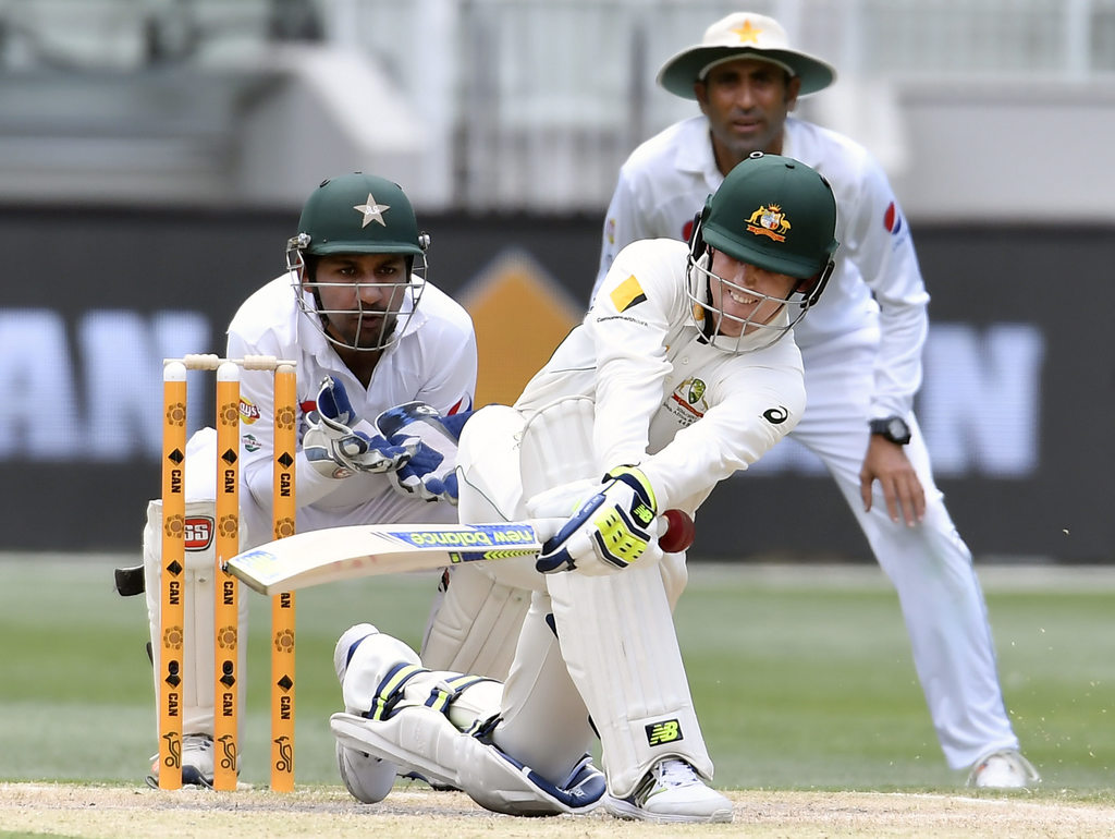 Pakistan's Sarfraz Ahmed, left, and Younis Khan, back as Australia's Nic Maddinson attempt a sweep shot on the fourth day of their seco...