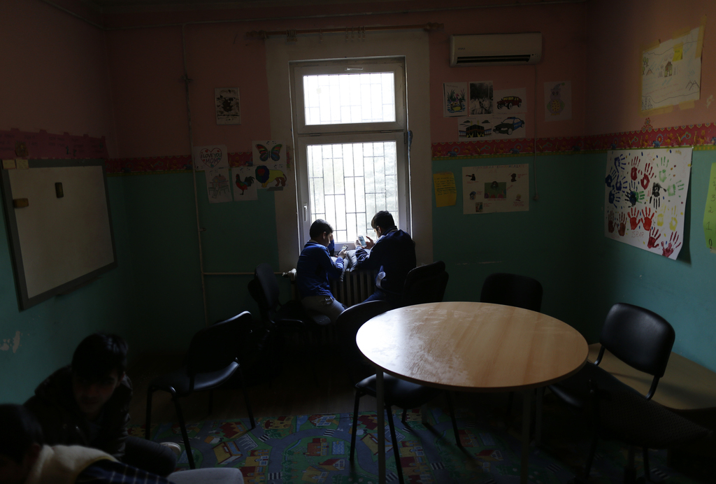 Migrant children look at mobile phones in a children's care center in Belgrade, Serbia, Wednesday, Dec. 21, 2016. Minors make up about ...