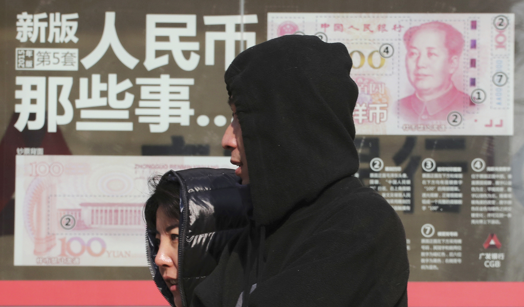 FILE - In this Thursday, Nov. 24, 2016, file photo, residents walk past a board highlighting the security markers on the latest Yuan no...