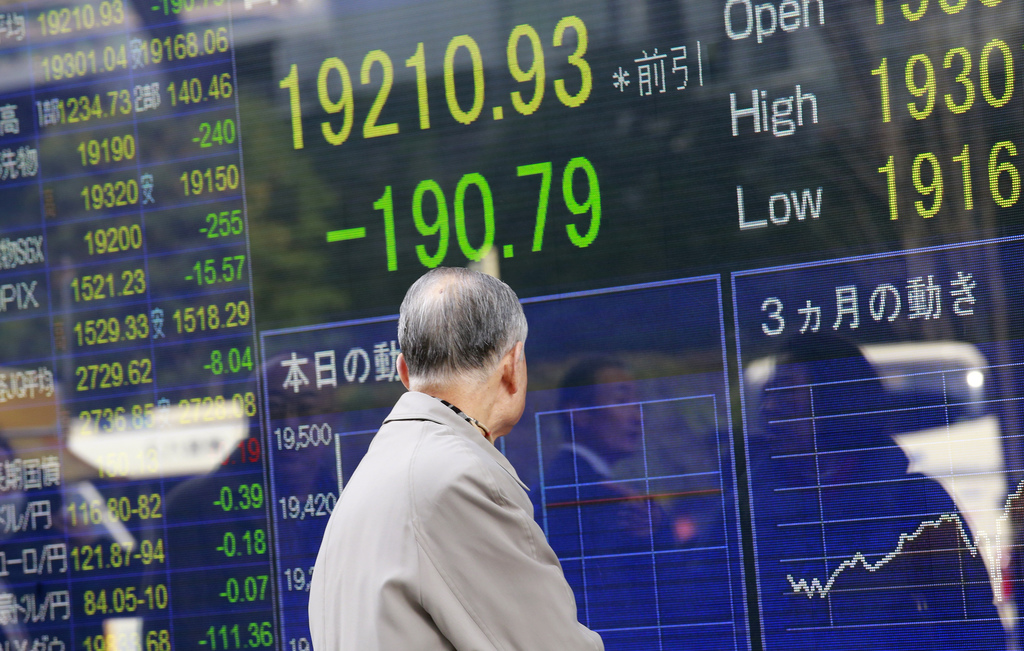 A man looks at an electronic stock indicator of a securities firm in Tokyo, Thursday, Dec. 29, 2016. Asian shares drooped in thin tradi...