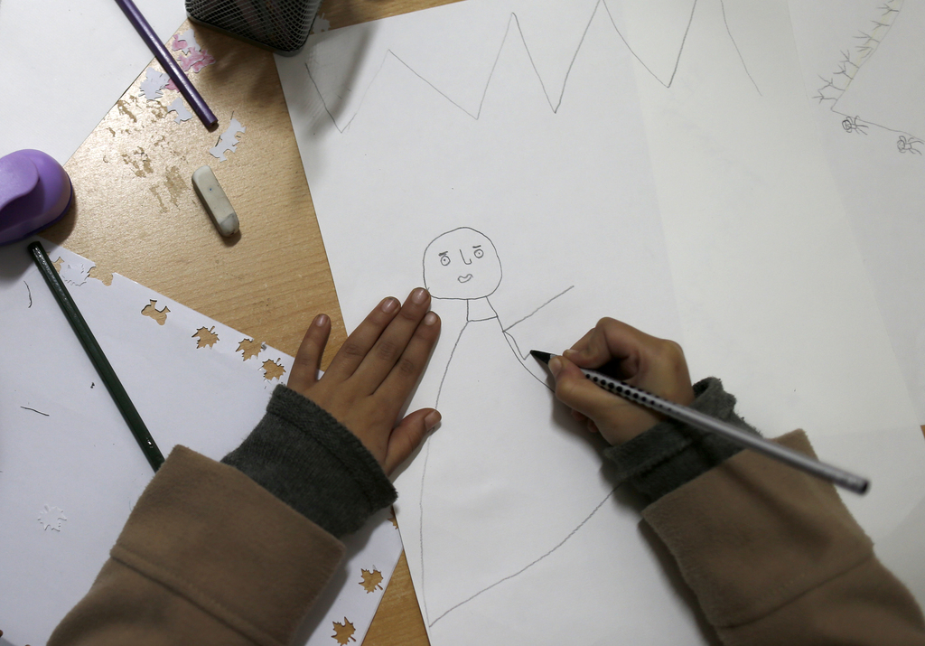 A migrant girl draws a picture during her stay in the Miksaliste hub for refugees and migrants, in Belgrade, Serbia, Wednesday, Dec. 21...