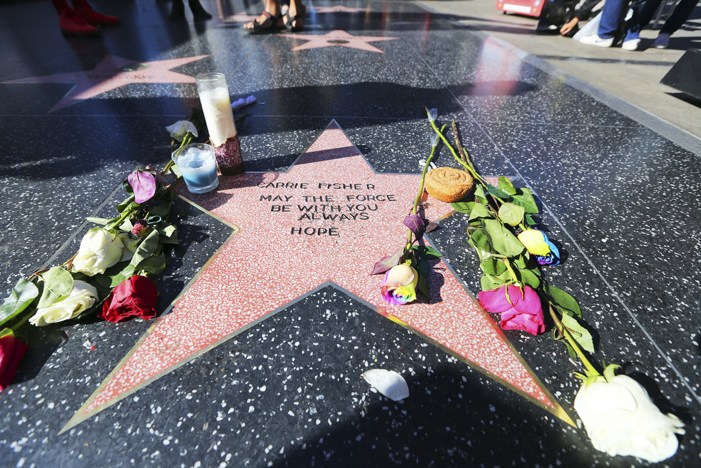 Flowers and candles adorn an impromptu memorial created on a blank Hollywood Walk of Fame star by fans of late actress and author Carri...