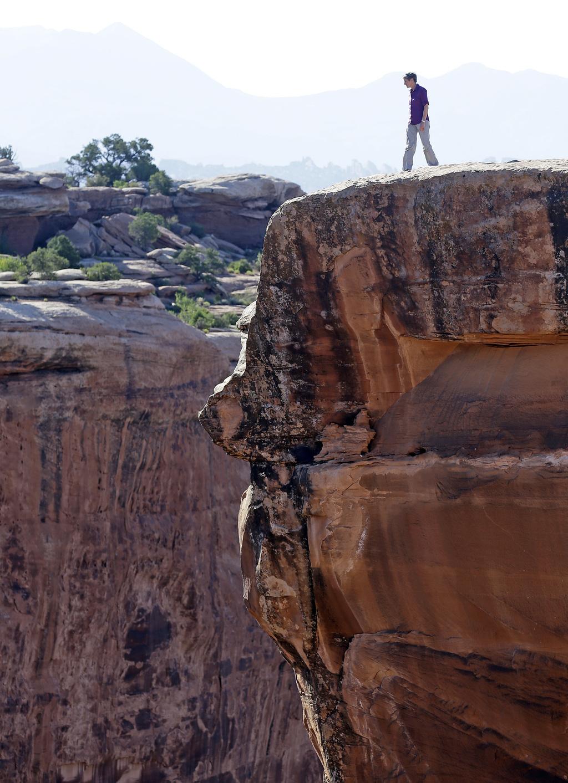 FILE - This July 14, 2016, file photo, U.S. Interior Secretary Sally Jewell looks in to a canyon at Gemini Bridges near Moab, Utah, dur...