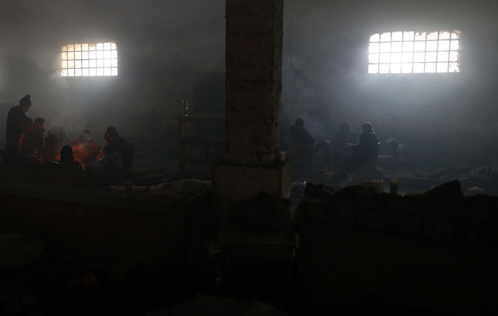 Migrants warm themselves by a fire in an abandoned warehouse, in Belgrade, Serbia, Tuesday, Dec. 20, 2016. Minors make up about 40 perc...
