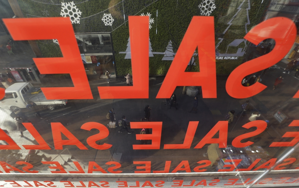 In this Wednesday, Dec. 28, 2016 photo, sale signs are displayed on a window of a store at a shopping district in Seoul, South Korea. S...
