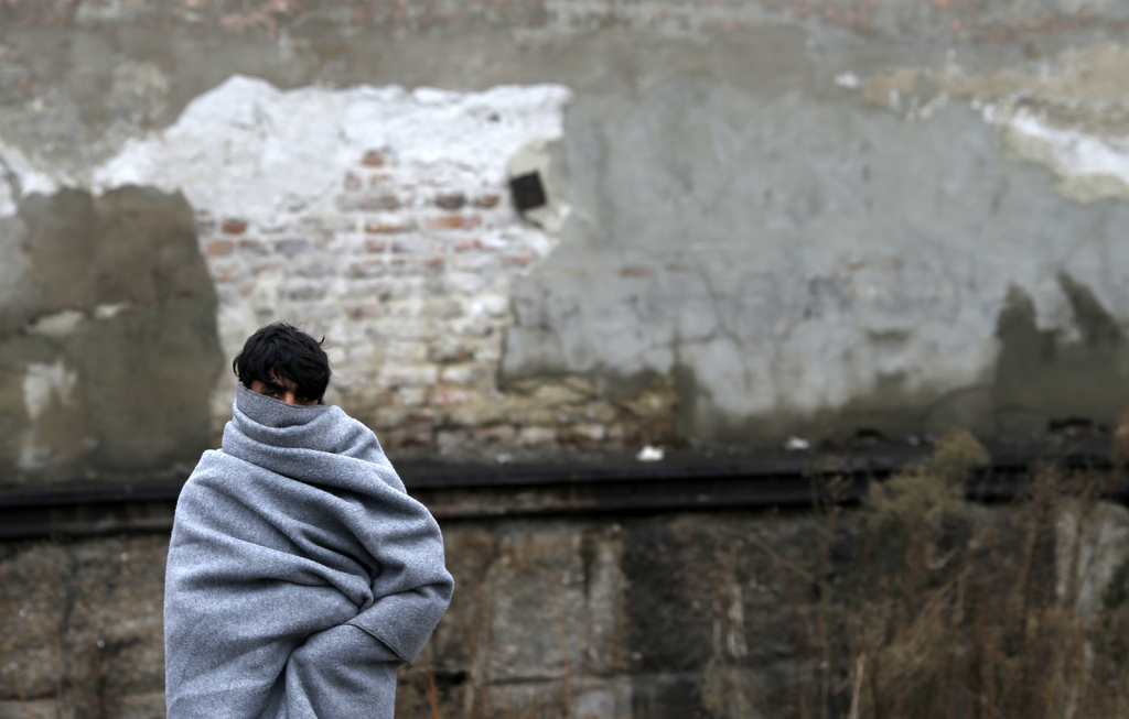 A migrant wrapped in a blanket walks in front of an abandoned warehouse, in Belgrade, Serbia, Tuesday, Dec. 20, 2016. Minors make up ab...