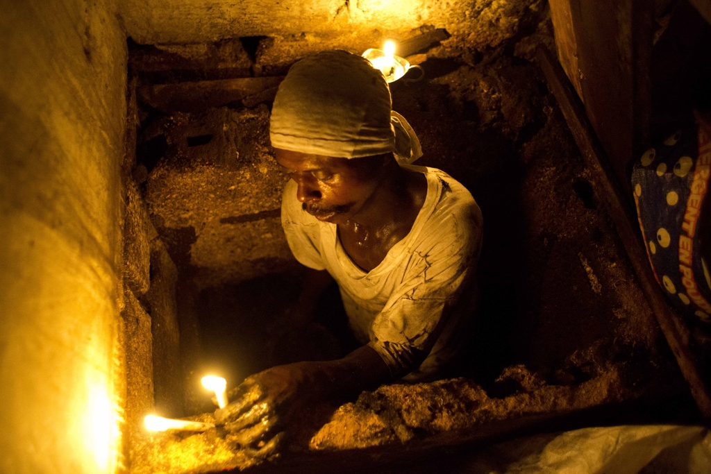 "In this Dec. 22, 2016 photo, Dieusel Gerlin, a""bayakou"", or waste cleaner, uses candles for illumination before descending into the pit..."