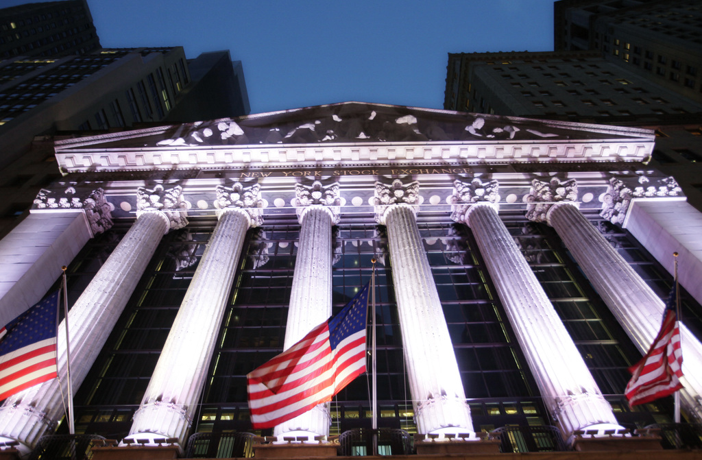 FILE - In this Wednesday, Oct. 8, 2014, file photo, American flags fly in front of the New York Stock Exchange. Global shares mostly fe...