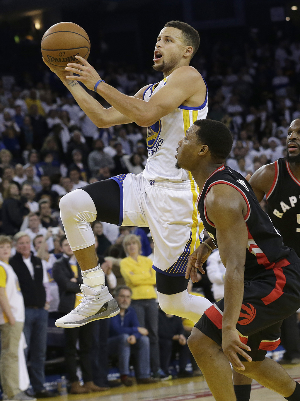 Golden State Warriors guard Stephen Curry, left, shoots against Toronto Raptors guard Kyle Lowry during the second half of an NBA baske...