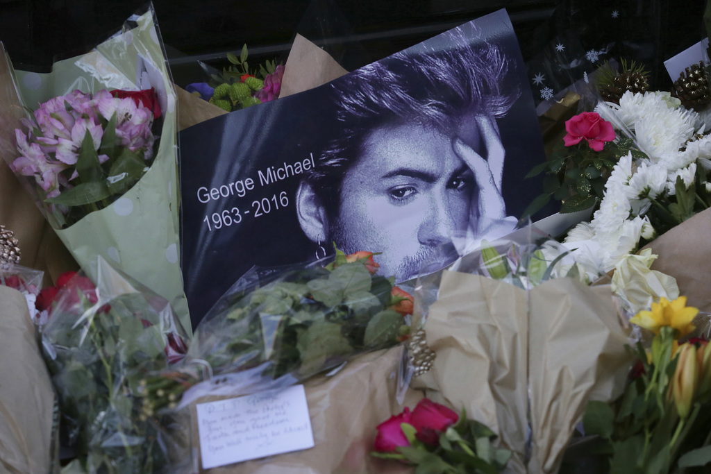 FILE - This Monday, Dec. 26, 2016 file photo shows tributes left outside the home of British musician George Michael in London. Michael...