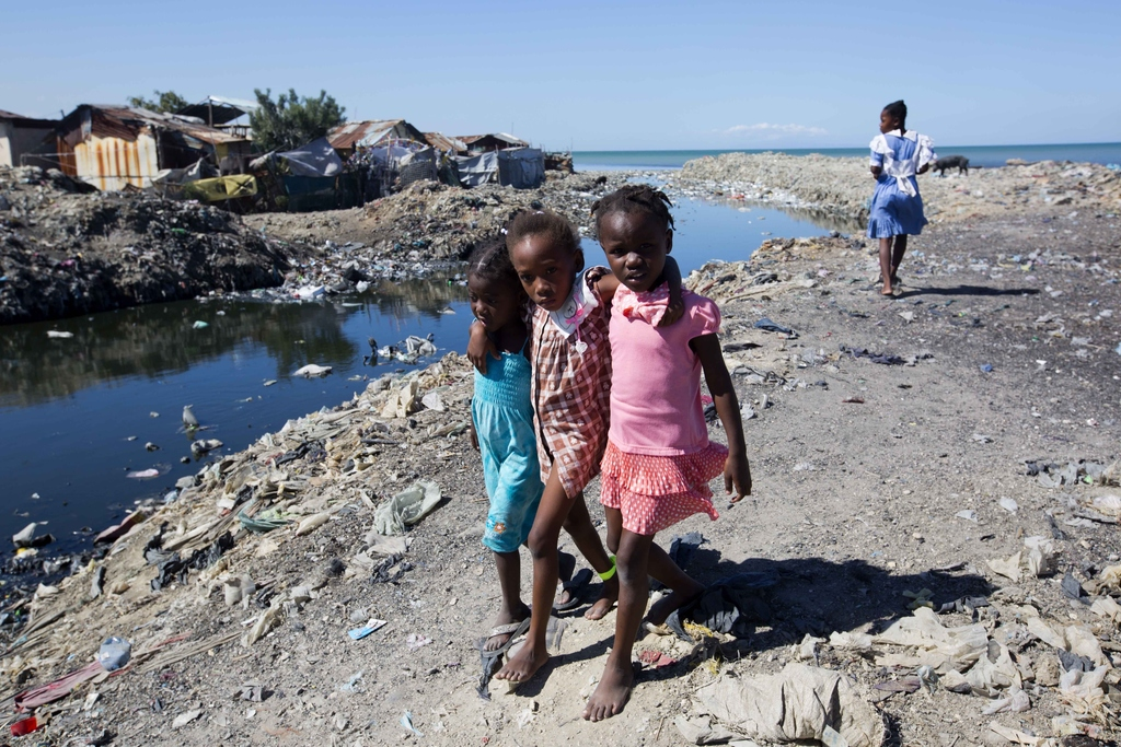 In this Dec. 25, 2016 photo, children walk arm and arm after openly defecating in a field near the shoreline in Cite Soleil slum, in Po...