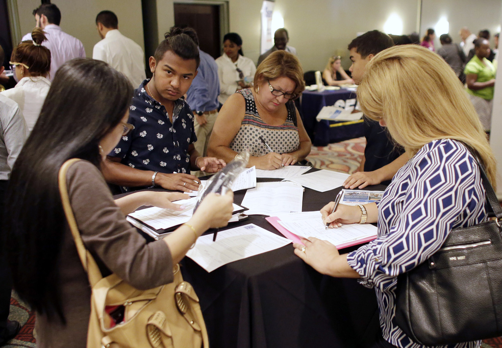 FILE - In this July 19, 2016, file photo, people fill out job applications at a job fair in Miami Lakes, Fla. On Thursday, Dec. 29, 201...