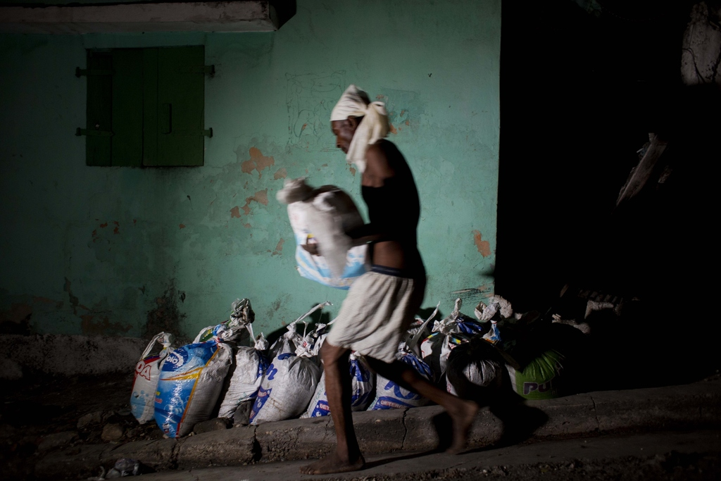 "In this Dec. 22, 2016 photo, a ""bayakou"", or human waste cleaner, carries a sack filled with human waste to be hauled away and dumped b..."