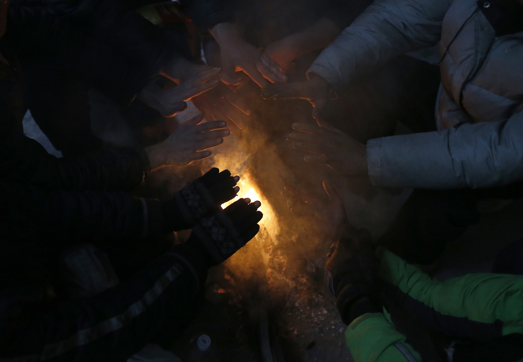 Migrants warm themselves by the fire in an abandoned warehouse, in Belgrade, Serbia, Tuesday, Dec. 20, 2016. Minors make up about 40 pe...