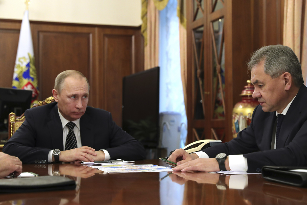 Russian President Vladimir Putin, left, listens to Defence Minister Sergei Shoigu in Moscow, Russia on Thursday, Dec. 29, 2016. Putin i...