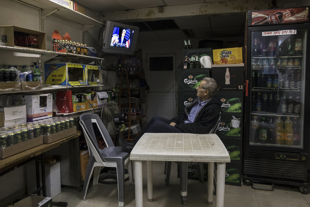 An Israeli grocery store owner watches  the US Secretary of State John Kerry speech at the State Department at Washington, in Sderot ne...