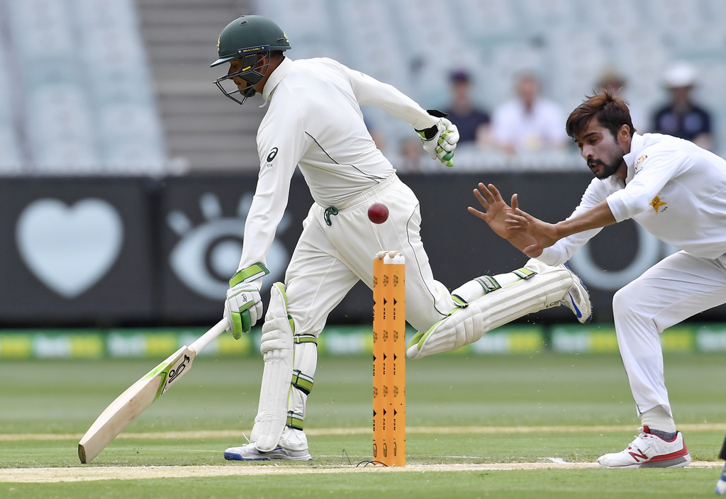 Australia's Usman Khawaja, left, makes a run as Pakistan's Wahab Riazon fields on the fourth day of their second cricket test in Melbou...
